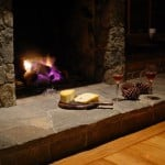 A cozy fire place with cheese and wine